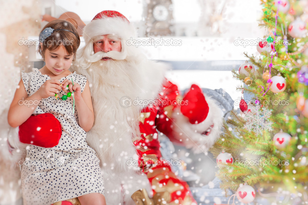 Christmas theme: Santa Claus and little girl having a fun. Indoors at home near christmas tree. — Stok fotoğraf #8208189