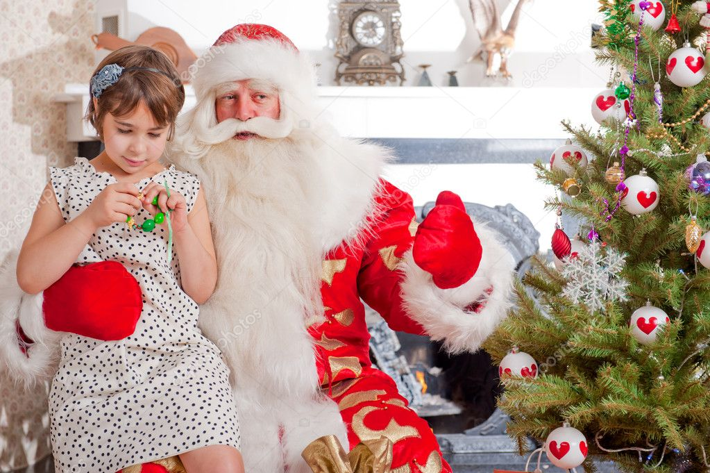 Christmas theme: Santa Claus and little girl having a fun. Indoors at home near christmas tree. — Stok fotoğraf #8208190