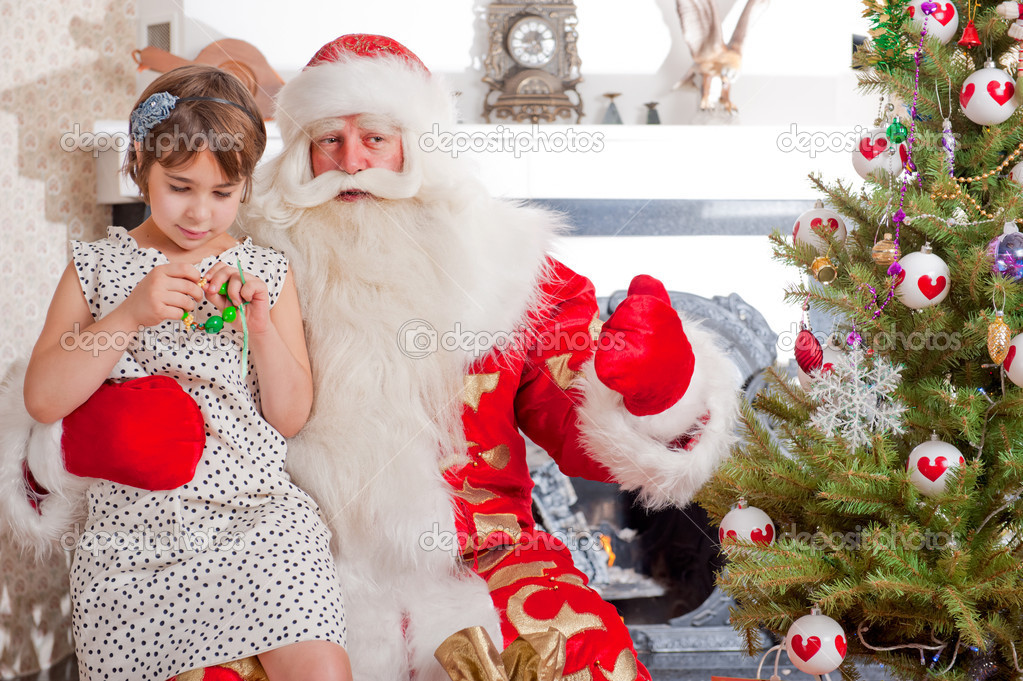 Christmas theme: Santa Claus and little girl having a fun. Indoors at home near christmas tree. — Stock fotografie #8208190