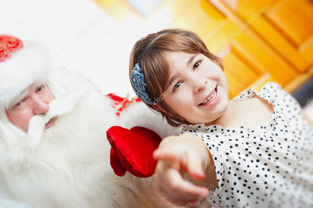Christmas theme: Santa Claus and little girl having a fun. Indoors at home near christmas tree. — Stock Photo #8208191