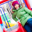 Portrait of young pretty playful woman riding down at playground - Foto de Stock  