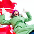 Portrait of young pretty playful woman riding down at playground — Stockfoto