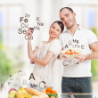 Stock Photo: Playful young couple in their kitchen preparing healthy food and