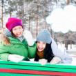 Two happy young girls having fun in winter park. Blank cloud bal — Stock Photo