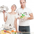 Playful young couple preparing healthy food and drinking wine is — 图库照片