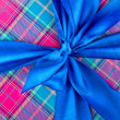 Big blue holiday bow on ornamental background - Stock Photo