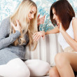 Two young women friends chatting at home. One showing to another — Stock Photo