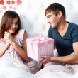 Happy young couple relaxing on a bed — Stock Photo #8660672