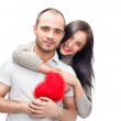 Happy young adult couple with red heart on white background, emb — Stock Photo