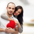Portrait of young couple with red heart standing at their home a — Stock Photo