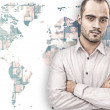A handsome business man against world map on background with man — Stock Photo