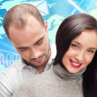 Portrait of young couple embracing. Standing against world map. - Stock Photo