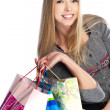 Side view of woman holding shopping bags against white backgroun - Stock Photo