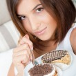 Smiling brunette woman eating some cake in the living room in he — Stock Photo #8661104