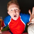 Stock Photo: Young man holding soccer ball and beer and watching tv translation