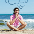 Portrait of young man sitting in lotus pose on sand on beach and — Stock Photo #8661650