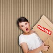 Closeup portrait of a young woman with boxes — Stock Photo #8661760