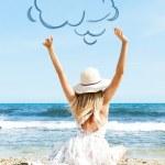 Portret van een jonge vrouw op het strand in de buurt van de zee zitten met h — Stockfoto