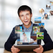 Portrait of young happy man sharing his photo and video files in — ストック写真
