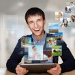 A technology man has images flying away from his modern tablet c - Stock Photo