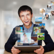 A technology man has images flying away from his modern tablet c — Stock Photo