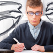 Stock Photo: High school - Young male student write notes in classroom. Desig