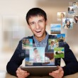 Portrait of young happy man sharing his photo and video files in - Stock Photo