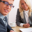 Stock Photo: Young successful smiling business are working in the offi