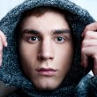 Portrait of young handsome man putting on warm pullover and look - Stock Photo