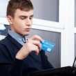 Handsome man holding credit card and using laptop for online sho — Stock Photo