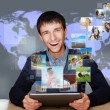 Stock Photo: A technology man has images flying away from his modern tablet c