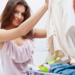Stock Photo: Beautiful young slim woman on the bed indoors unpacking clothes