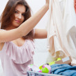 Beautiful young slim woman on the bed indoors unpacking clothes — Stock Photo