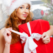 Christmas woman near a Christmas tree holding big gift box while — Stock Photo #8663629
