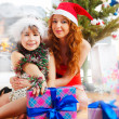 Little girl with her mother sitting together near christmas tree — Stock Photo #8663644