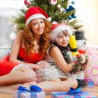 Little girl with her mother sitting together near christmas tree — Stock Photo #8663648