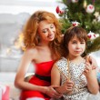 Mother and her daughter sitting together near christmas tree — Stock Photo