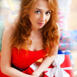 Christmas woman near a Christmas tree holding big gift box while — Stock Photo #8663686