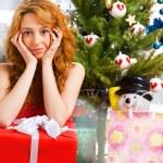 Christmas woman near a Christmas tree holding big gift box while — Stock Photo #8663695