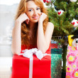 Christmas woman near a Christmas tree holding big gift box while — Stock Photo