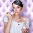 Portrait of attractive young adult woman applying blusher agains — Stock Photo