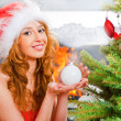 Christmas woman near a Christmas tree holding Christmas toy whil — Stock Photo #8663744