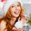 Christmas woman near a Christmas tree holding Christmas toy whil — Stock Photo #8663752
