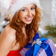 Christmas woman near a Christmas tree holding big gift box while — Stock Photo #8663806