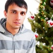 Young calm man sitting in front of Christmas tree — Stock Photo