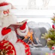 Santa sitting at the Christmas tree, near fireplace and reading — Stock Photo
