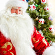Stock Photo: Santa sitting at the Christmas tree, fireplace and looking at ca