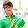 Portrait of young man inside shopping mall with gift box sitting — Stock Photo #8663945