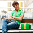 Portrait of young man inside shopping mall with gift box sitting — Stock Photo #8663950