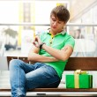 Stock Photo: Portrait of young man inside shopping mall with gift box sitting